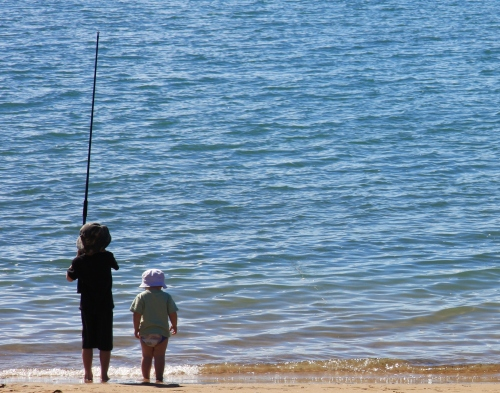 Two kids fishing at a lake